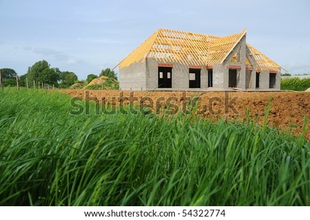 A new house under construction in countryside - stock photo