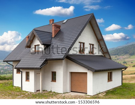 A new house with a garage in a rural area - stock photo