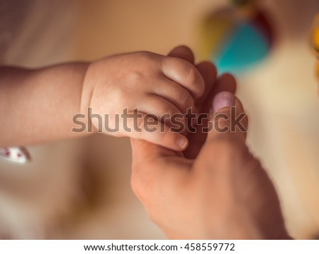 A new mother is holding his newborn infant baby's hand closeup/the joy of motherhood / happy moments