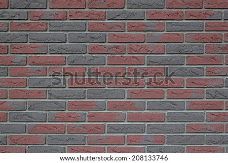 A new red and gray brick wall with concrete seam. - stock photo