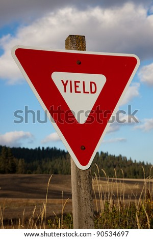 A new red yield sign is bolted to an old mossy post on a country road with grassy fields and tall trees in the distance.