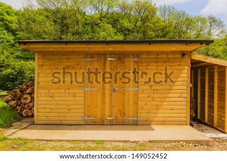 a new wooden shed in the countryside - stock photo