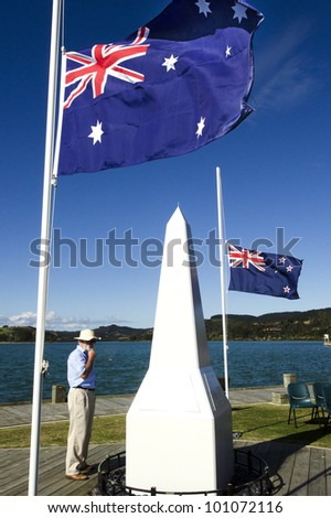 A New Zealander person under the national flags of Australia and New Zealand during a National War Memorial Anzac Day services in New Zealand. - stock photo