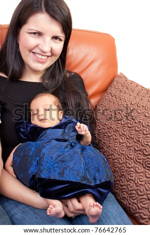 A newborn baby being held in the arms of her mother. - stock photo