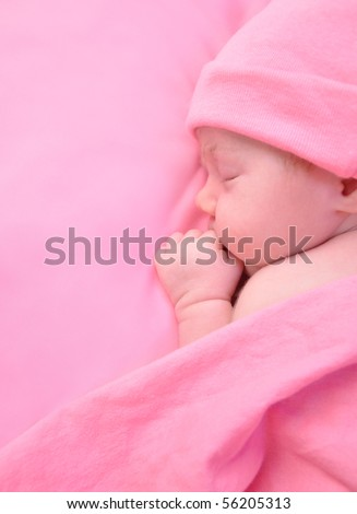 A newborn baby girl is sleeping on a pink blanket and is wearing a hat. Use it for a childhood, parenting  or innocence theme. Add your text message to the side. - stock photo