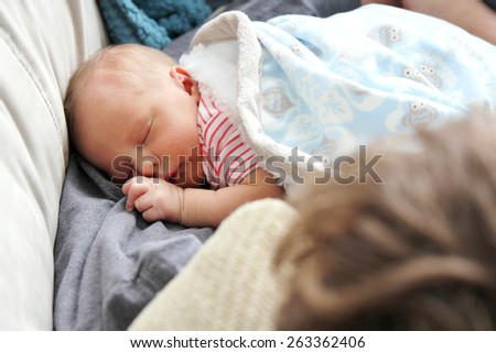 A newborn baby girl is sleeping on her father's lap at home. - stock photo
