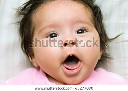 A newborn baby girl with a surprised look on her face - stock photo