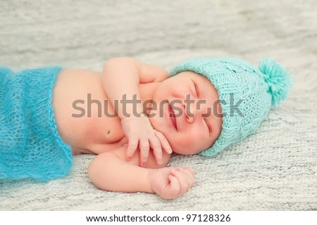 A newborn baby is wearing a blue hat and laying down sleeping on a soft white background. Soft focus, shallow DoF.