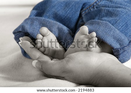a newborn baby's small feet being held by mommy - stock photo