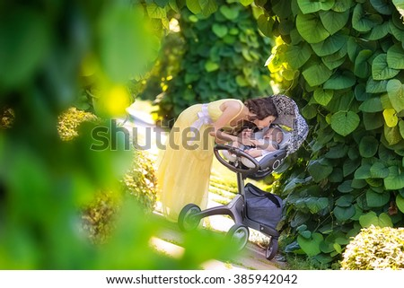 a newborn baby with a beautiful mother in the park - stock photo