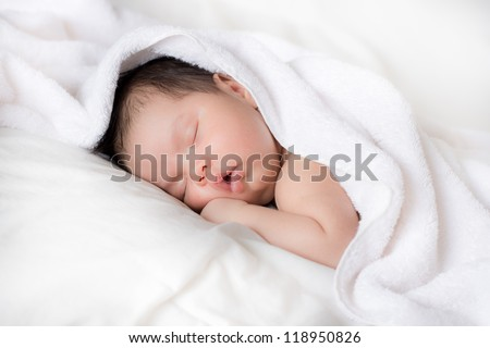 A newly bathed newborn baby sleeps in a white towel - stock photo