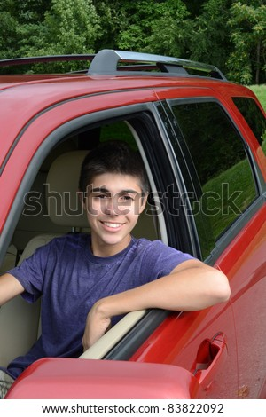 A newly licensed teenage male driver sits in his shiny new red car. Close up in vertical format showing the young caucasian man smiling as he sits behind the wheel. - stock photo