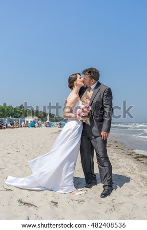a newly married couple kissing each other on the Baltic beach / Newlyweds seaside / Newlyweds