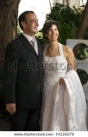 A newly married couple smile away from the camera and look away from the camera, while still in their wedding clothes. A scenic area fills the background. - vertically framed - stock photo