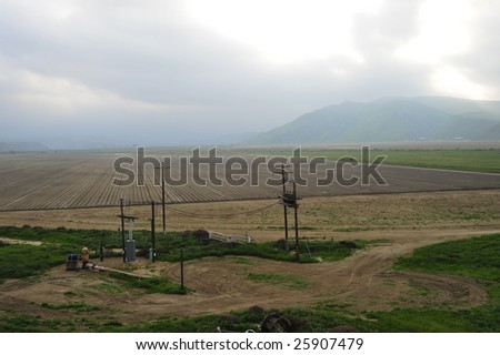 A newly planted California farm field with electric substation for local power - stock photo