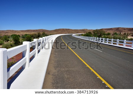 A newly tarred road with white fence in Namib desert, Namibia, Africa - stock photo
