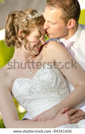 A newly wed Bride and Groom sharing a few moments together after their wedding in the late evening sun - stock photo