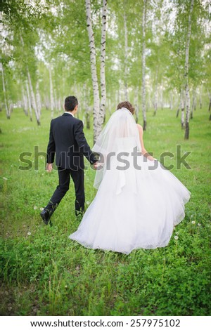 A newly wed couple walking through forrest, holding hands