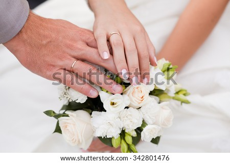 A newly weding couple place their hands on a wedding bouquet showing off their wedding rings. - stock photo
