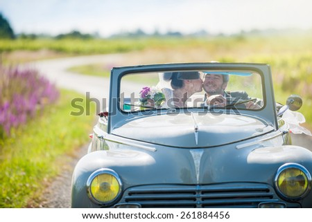A newlywed couple is driving a retro car on a country road for their honeymoon. The bride is kissing the groom. - stock photo