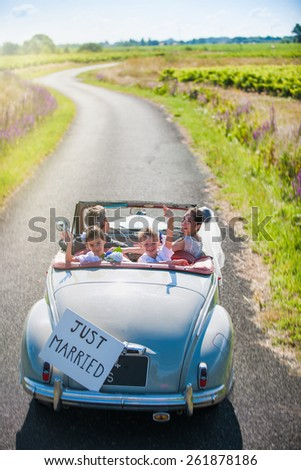 A newlywed couple is driving a retro car on a country road with their two beautiful children. - stock photo