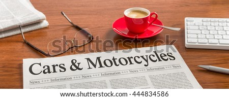 A newspaper on a wooden desk - Cars and Motorcycles - stock photo