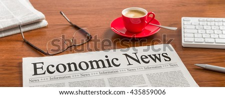 A newspaper on a wooden desk - Economic News - stock photo