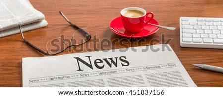A newspaper on a wooden desk - News - stock photo