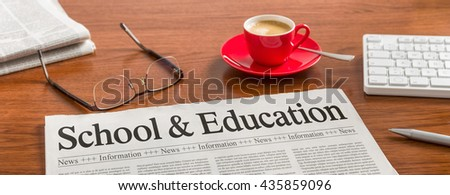 A newspaper on a wooden desk - School and Education - stock photo