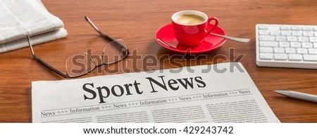 A newspaper on a wooden desk - Sport News - stock photo