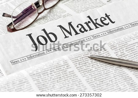 A newspaper with the headline Job Market - stock photo