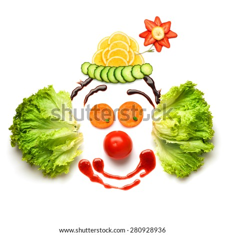 A nice and funny edible clown, made of strawberries, lemons, salad and so on. - stock photo