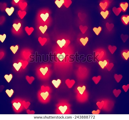 a nice background with unfocussed lights blurred into the shape of hearts - holidays like valentine's day or wedding announcements or romantic cards toned with a retro vintage instagram filter effect - stock photo