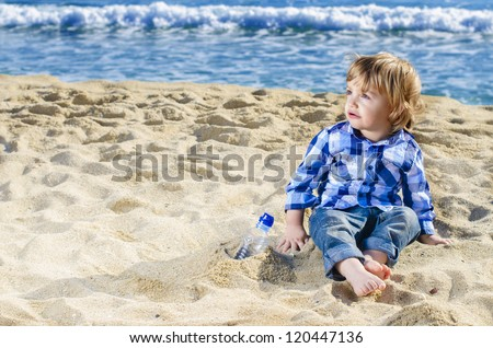 A nice boy looking astonished on a beach