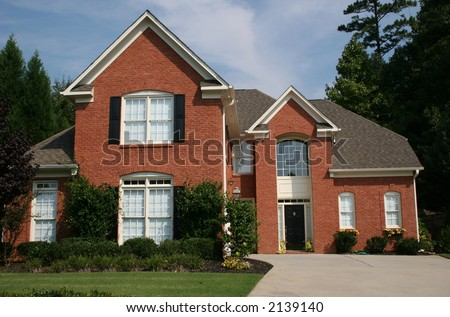 A nice brick house against blue sky - stock photo