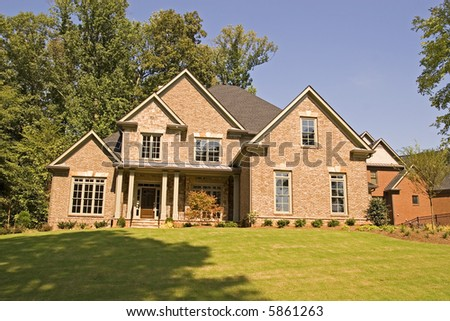 A nice brick house on a shady landscaped hill - stock photo