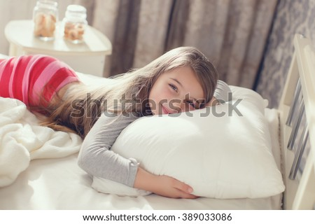 A nice child girl enjoys sunny morning. Good morning at home. Child girl wakes up from sleep. A close up portrait of a sweet smiling little girl waking up and lying in bed in the morning