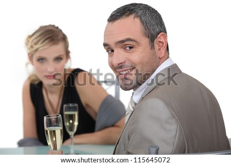 A nice couple having champagne in a restaurant. - stock photo