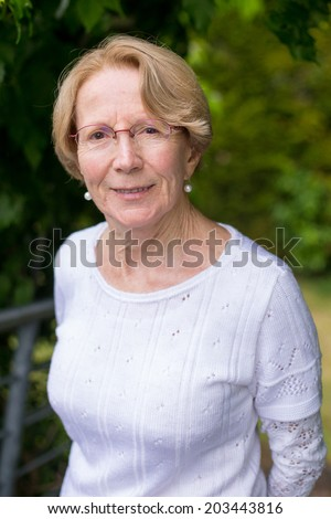 A nice elderly woman is smiling at the camera in a beautiful gar - stock photo