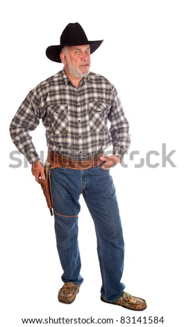 A nice full body image of a real cowboy with a gun on his side.