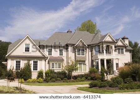 A nice grey brick house on a landscaped lot - stock photo