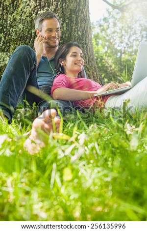 A nice grey hair man and a woman are sitting in the grass, listening some music on their computer. The couple is sitting against a tree, enjoying the shadow of the tree in a sunny day. - stock photo