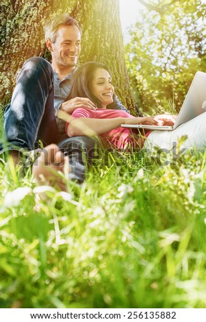 A nice grey hair man and a woman are sitting in the grass, looking at their computer. The man is sitting against a tree while his girlfriend is laying against him.  - stock photo