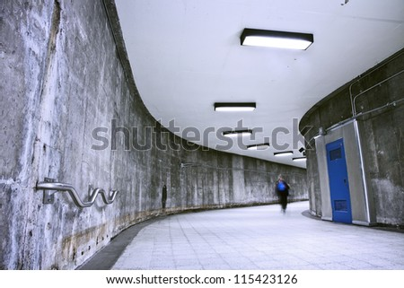 A nice grunge corridor with a blue door. It was a very dark and weird place. This passage is part of a Montreal metro station. This is how to transit from a metro to an other (to change line). - stock photo
