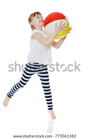A nice little girl is playing with a big inflatable ball. The concept of a happy childhood, family recreation in nature, fitness and exercise. Isolated on white background.