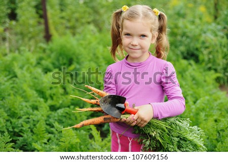 A nice little girl working in a kitchen-garden - stock photo