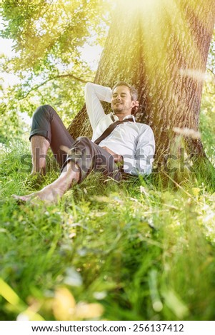 A nice looking man is sitting against a tree in the grass, looking like he is dreaming. He is relaxing, enjoying the shadow of the tree in a sunny day. - stock photo
