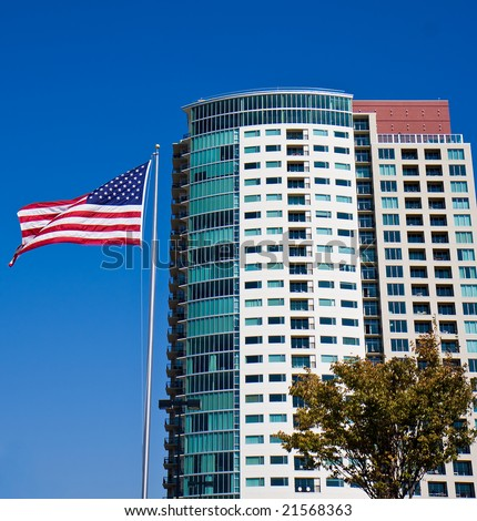 A nice new high rise condominium and an American Flag - stock photo