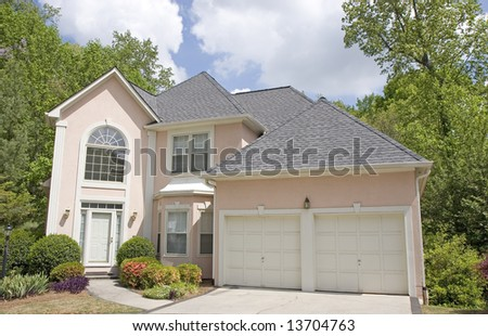 A nice pink stucco house with blue sky and clouds