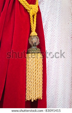 A nice red velvet curtain tied back by a string and tassel - stock photo